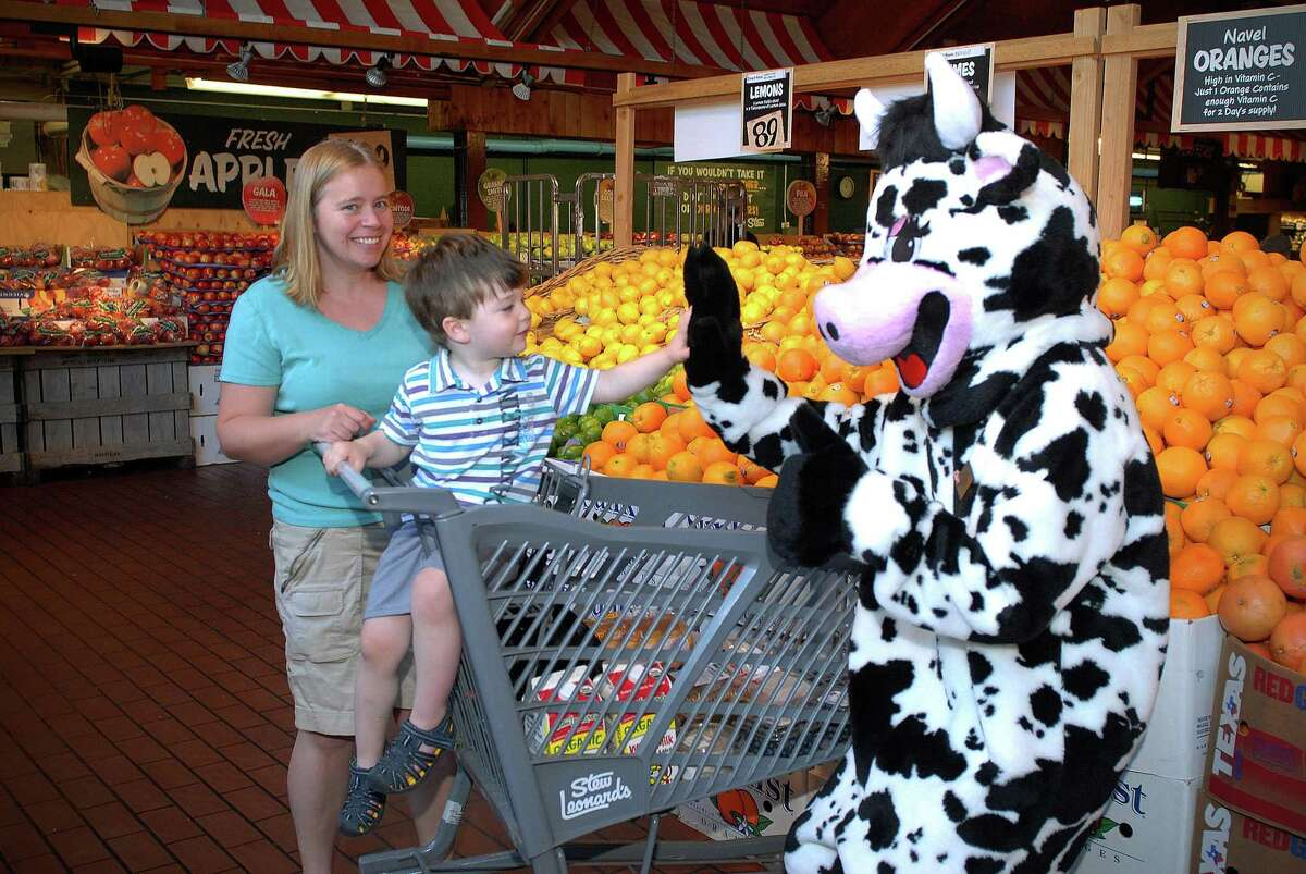 """Danielle Hildbrand and son Thomas of Stamford greet Billy Reyes wearing """"Clover"""" the cow costume at Stew Leonard's in Norwalk, Conn. on Monday June 2, 2014."""