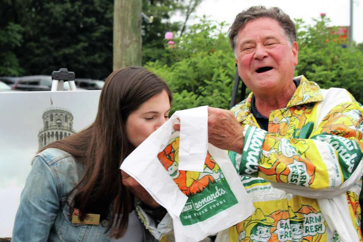 Stew Leonard Jr., the president and CEO of Stew Leonard's andhis daughter Blake kisssingle-use plastic bags goodbye at an event on Monday, July 8, 2019, the first day plastic bags were officially banned in Norwalk.