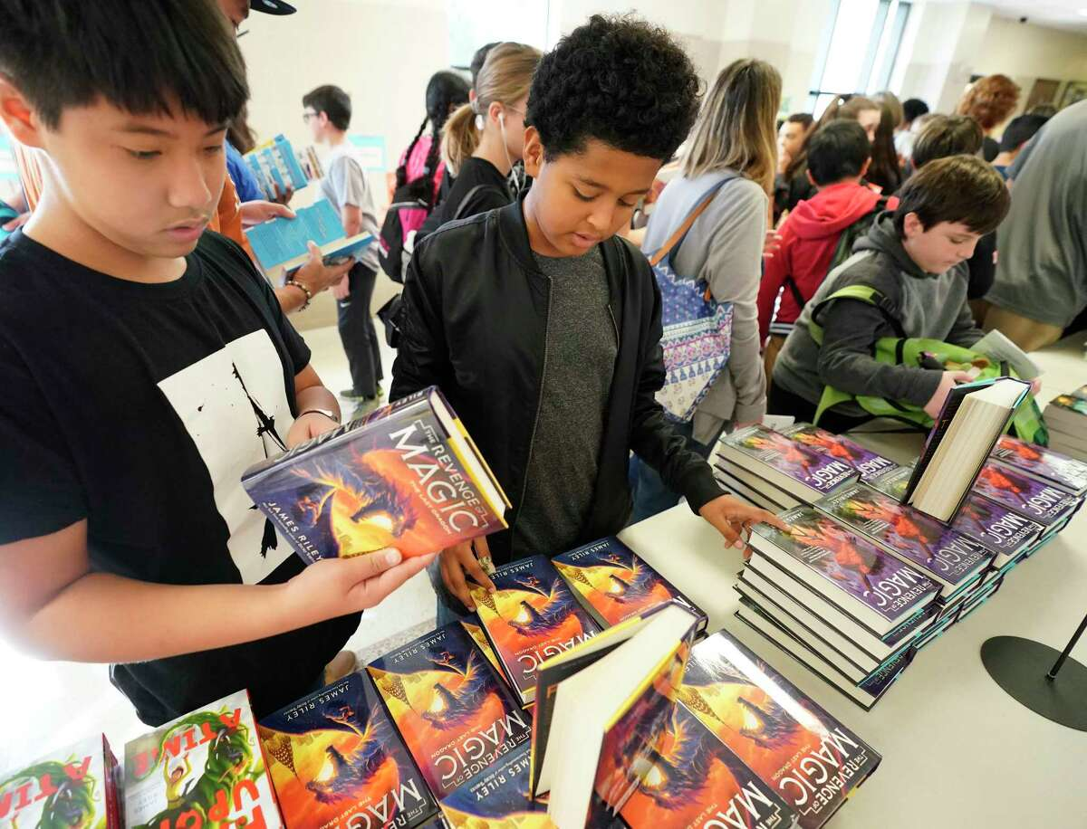 Richard Le, 12, left, and Hussai Arias, 11, right, both sixth graders at Morris Middle School in Pasadena ISD look at books during the Tweens Read Book Festival held at Pasadena Memorial High School, Saturday, Oct. 19, 2019, in Pasadena.