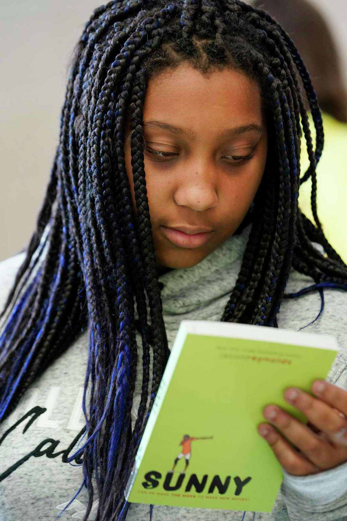 Taylor Biggers, 13, an eighth grader at Victory Lakes Intermediate in Clear Creek ISD looks a book during the Tweens Read Book Festival held at Pasadena Memorial High School, Saturday, Oct. 19, 2019, in Pasadena.