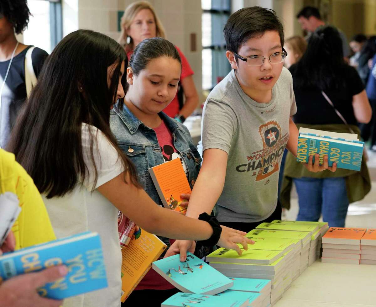Tri Nguyen, 12, right, a seventh grader at Truitt Middle School in Houston ISD reaches for a book during the Tweens Read Book Festival held at Pasadena Memorial High School, Saturday, Oct. 19, 2019, in Pasadena.