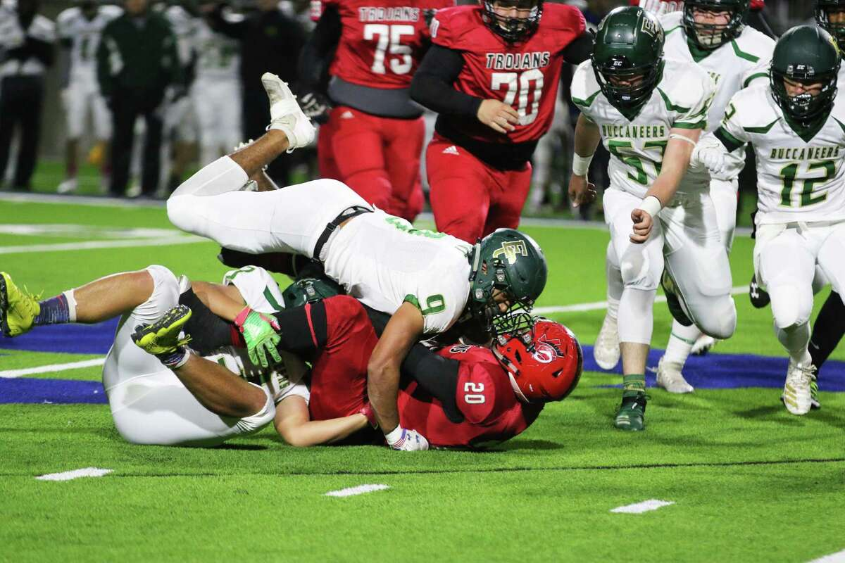 East Chambers linebacker Isaiah Hart comes face to face with Coldspring Oakhurst's running back Contavious Parker-Harden when he fell on top of him in Thursday's bi-district game. The Buccaneers won the game, 42-20.