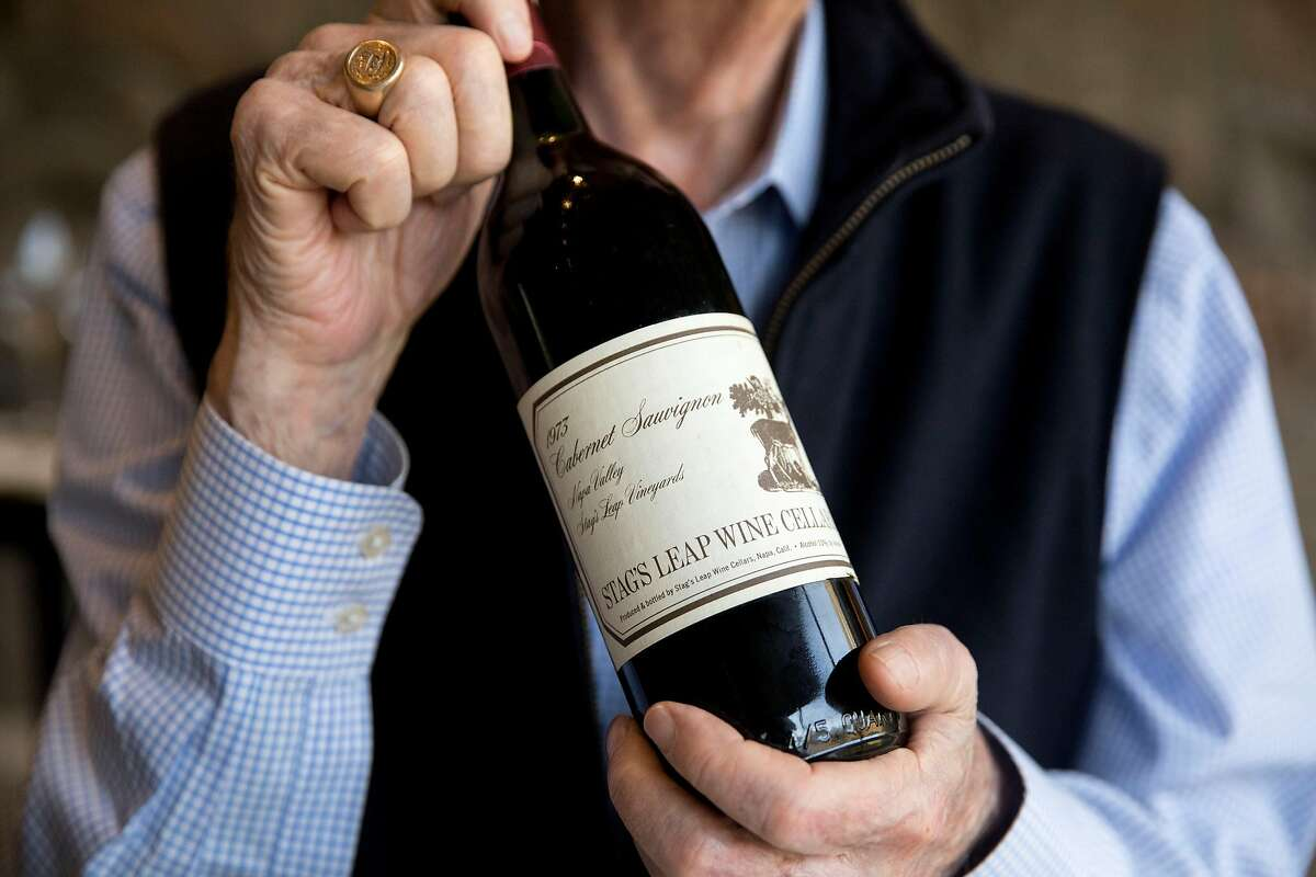 Warren Winiarski, who founded Stag's Leap Wine Cellars and later sold it, holds up a bottle of the Cabernet Sauvignon he made that won the famous Judgment of Paris.