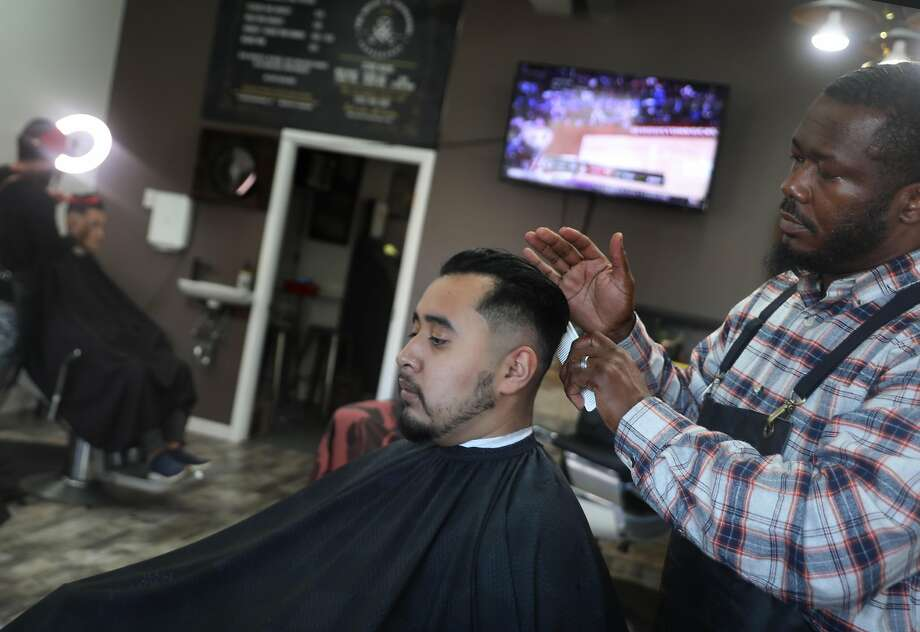 Abner Aranivar (middle) gets a haircut from barber Cyrus Wimpye (right) at the House of Handsome Barbershop in the Excelsior in 2019. Photo: Liz Hafalia / The Chronicle
