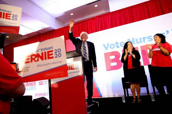 Sen. Bernie Sanders waves to the crowd after delivering a speech during the National Nurses United endorsement event for Sanders, at Lake Merritt Tower, located at 155 Grand Ave., in Oakland, Calif., on Friday, November 15, 2019. On stage with Sanders is Bonnie Castillo (second from right), a registered nurse and executive director, National Nurses United, California Nurses Association/National Nurses Organizing Committee, and Zenei Triunfo-Cortez (right), a registered nurse and member of the California Nurses Association/National Nurses Organizing Committee's Council of Presidents. NNU, the nation's largest union for registered nurses, officially announced its endorsement of Sanders, who's running for president of the United States.