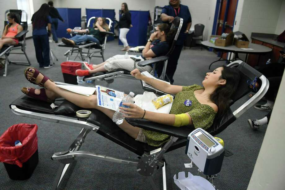 Trinity Moya, 18, right, who will be attending Lone Star College - Cy-Fair in the Fall, donates blood during the Gulf Coast Regional Blood Center blood drive held for victims of the El Paso shooting at the Berry Center on August 7, 2019. Photo: Jerry Baker, Houston Chronicle / Contributor / Houston Chronicle
