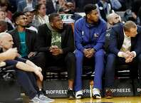 Golden State Warriors' Jacob Evans III, Kevon Looney, Glenn Robinson III  and Alan Smailigic on bench against Utah Jazz during NBA game at Chase Center in San Francisco, Calif., on Monday, November 11, 2019.