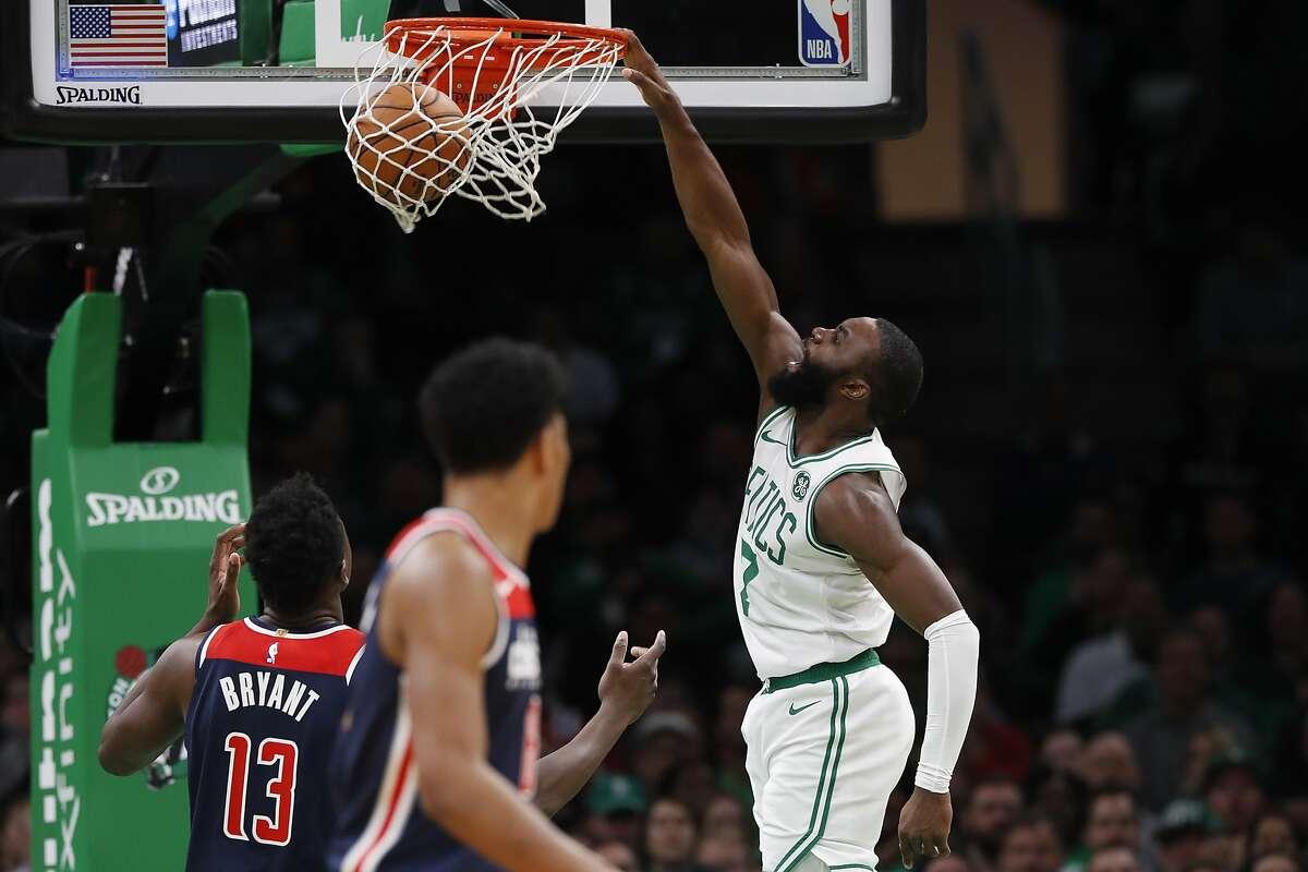 Boston Celtics' Jaylen Brown dunks as Washington Wizards' Thomas Bryant (13) watches during the fourth quarter of an NBA basketball game Wednesday, Nov. 13, 2019, in Boston. (AP Photo/Winslow Townson)