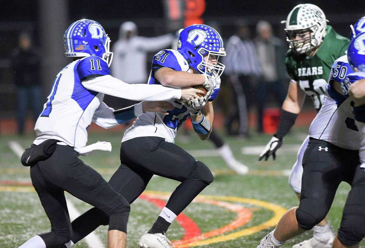 Darien quarterback Peter Graham (11) hands off to Will Kirby (21) who carries for short gain in the first half against Norwalk in a FCIAC football game at Norwalk High School Testa Field on Nov. 15, 2019 in Norwalk Connecticut.