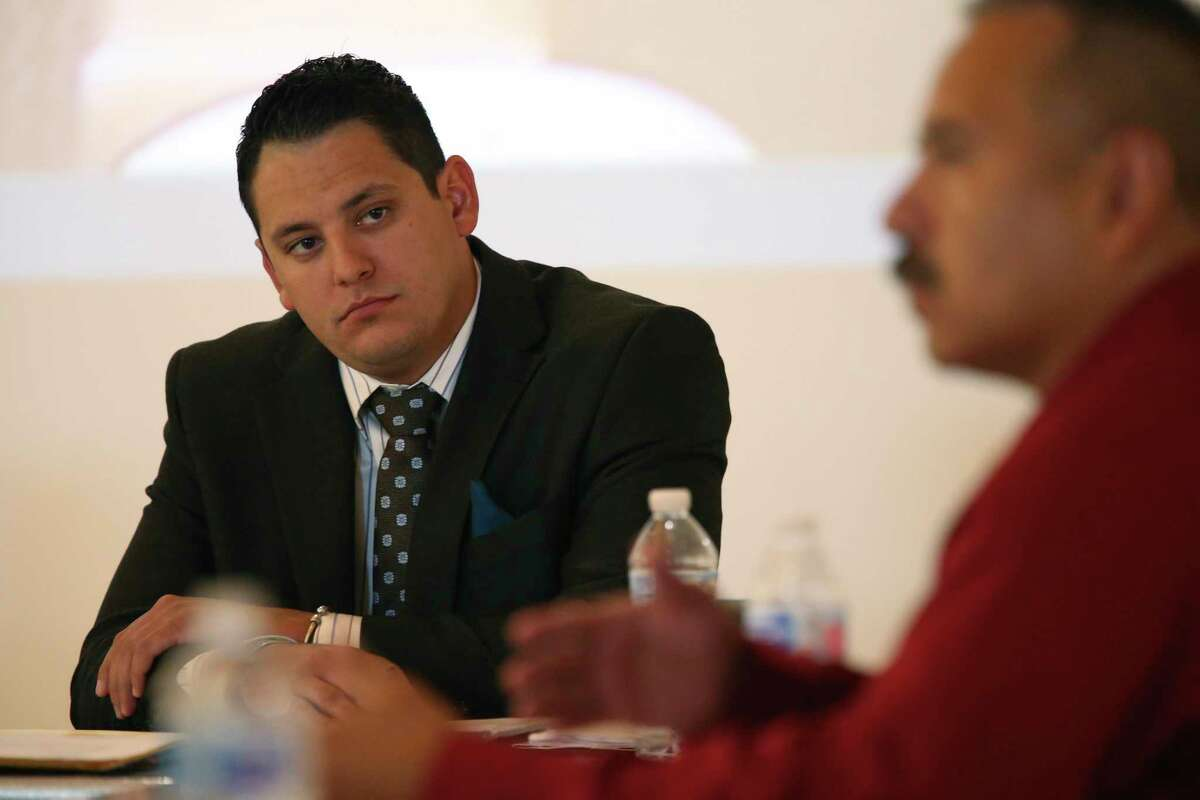 Former San Antonio police officer Justin Ayars, left, watches Detective John Doporto during his arbitration hearing in June.