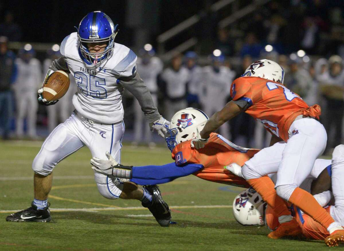 Fairfield Ludlowe's James Fiammetta (35) tries to get past the grasp of Danbury's Tyrell Jones (4) in the football game between Fairfield Ludlowe and Danbury high schools, Friday night, November 15, 2019, at Danbury High School, Danbury, Conn.