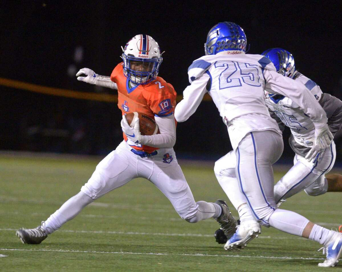 Danbury's Malachi Hopkins (2) tries to cut back on Fairfield Ludlowe's Jack Morison (25) and James Fiammetta (35) in the football game between Fairfield Ludlowe and Danbury high schools, Friday night, November 15, 2019, at Danbury High School, Danbury, Conn.