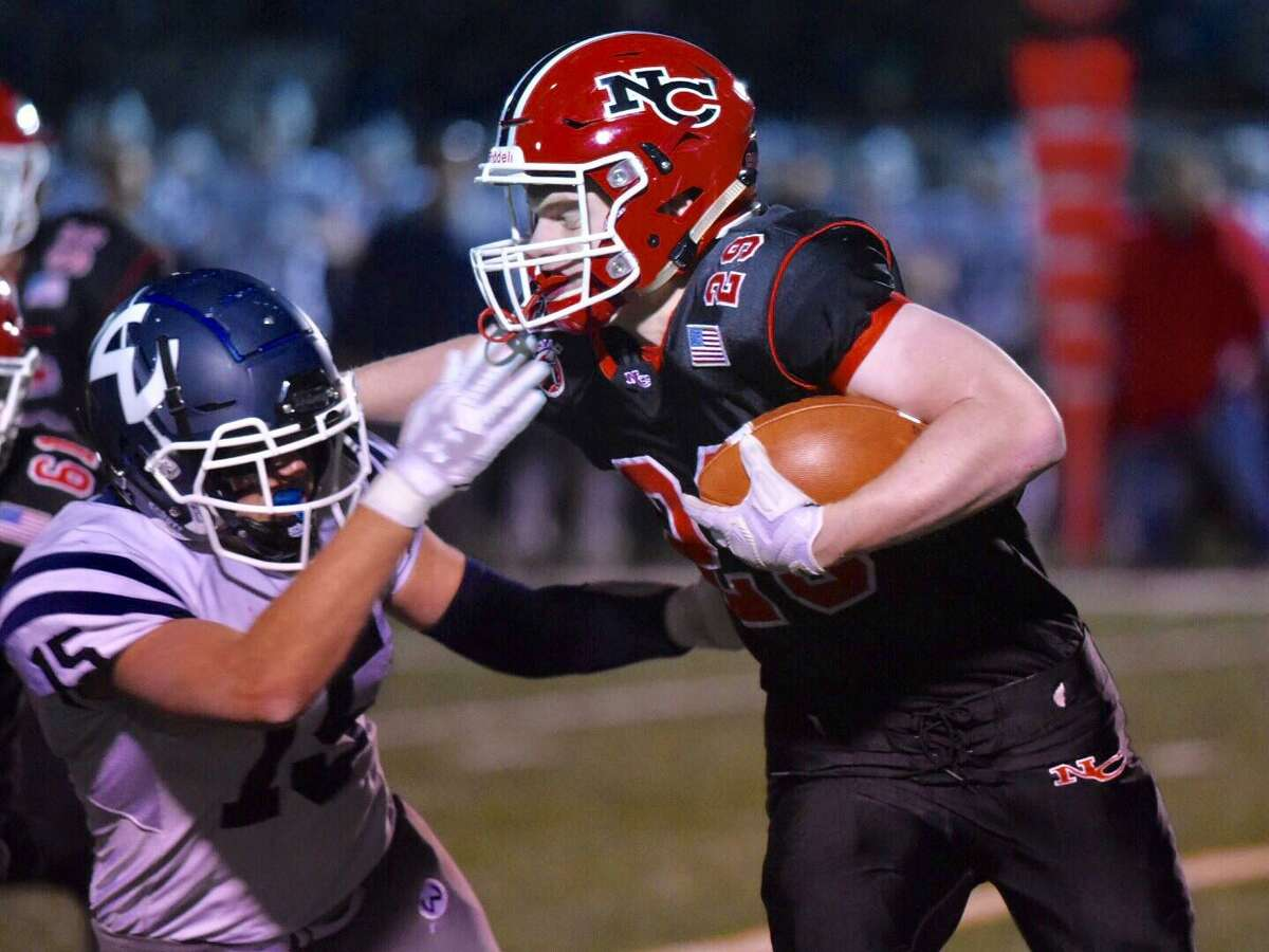 New Canaan's John Wise (29) runs with the ball while Wilton's Kyle Hyzy (15) defends during a football game at Dunning Field on Friday, Nov. 15, 2019.