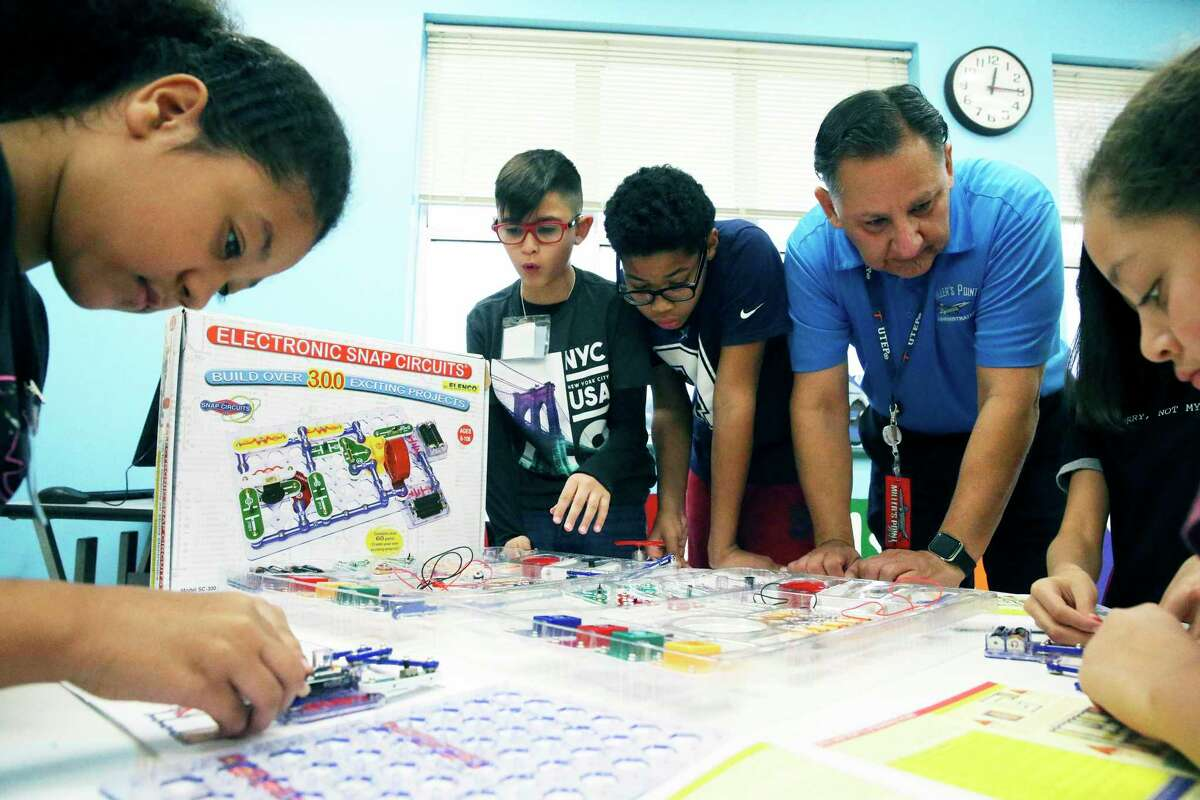 Jorge Gallegos observes an electronics exercise as he helps students in the STEAM (Science Technology, Engineering, Arts and Math) classroom at Miller's Point Elementary School last November. San Antonio's larger school districts are planning to offer a return to in-person classes this summer.