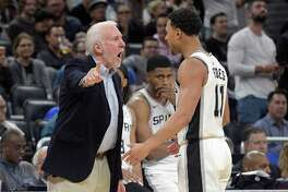 Spurs coach Gregg Popovich confronts guard Bryn Forbes after an Orlando score as forward Rudy Gay watches.