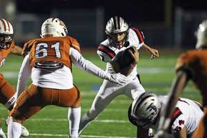 Falcons quarterback K.K. Brashears looks for running room as the Maverick defense moves in on him.