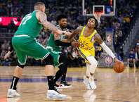Golden State Warriors guard D'Angelo Russell (0) while defended by Boston Celtics guard Marcus Smart (36) and forward Daniel Theis (27) in the first period of an NBA game at Chase Center on Friday, Nov. 15, 2019, in San Francisco, Calif.