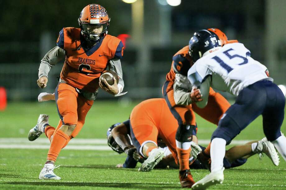 iBrandeis quarterback Jordan Battles, left, picks up yardage n the second half of their 6A Division II first round playoff game with Johnson at Farris Stadium on Friday, Nov. 15, 2019. Brandeis beat Johnson 42-28. Photo: Marvin Pfeiffer, Staff Photographer / Express-News 2019
