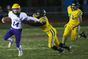 Live Oak High School quarterback Tony Vallejo, left, is chased down by Paradise High School's John Webster during the first half of a Northern California Division III playoff game in Paradise, Calif., Friday, Nov. 15, 2019. The Paradise High Bobcats had an undefeated season and made it to the playoffs a year after the deadliest wildfire in California history that killed dozens and destroyed nearly 19,000 buildings including the homes of most of the players. (AP Photo/Rich Pedroncelli)