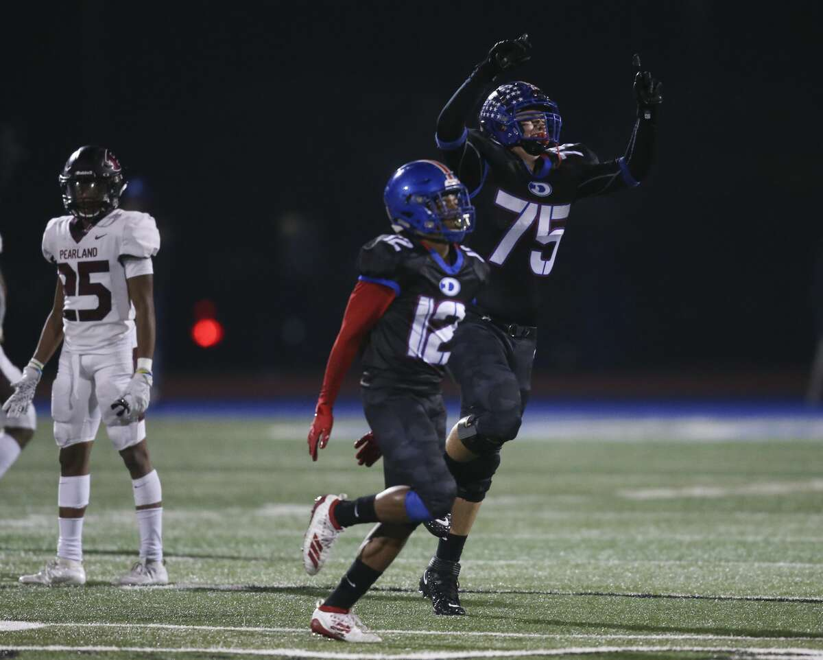 Dickinson Gators Canon Boone (75) and Kai German (12) celebrate the win over the Pearland Oilers on November 15, 2019 at in Dickinson, TX. Dickinson won 28 to 23.