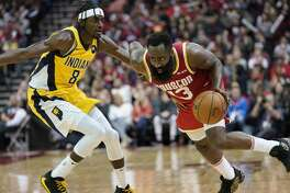 Houston Rockets' James Harden (13) drives toward the basket as Indiana Pacers' Justin Holiday (8) defends during the second half of an NBA basketball game Friday, Nov. 15, 2019, in Houston. The Rockets won 111-102. (AP Photo/David J. Phillip)