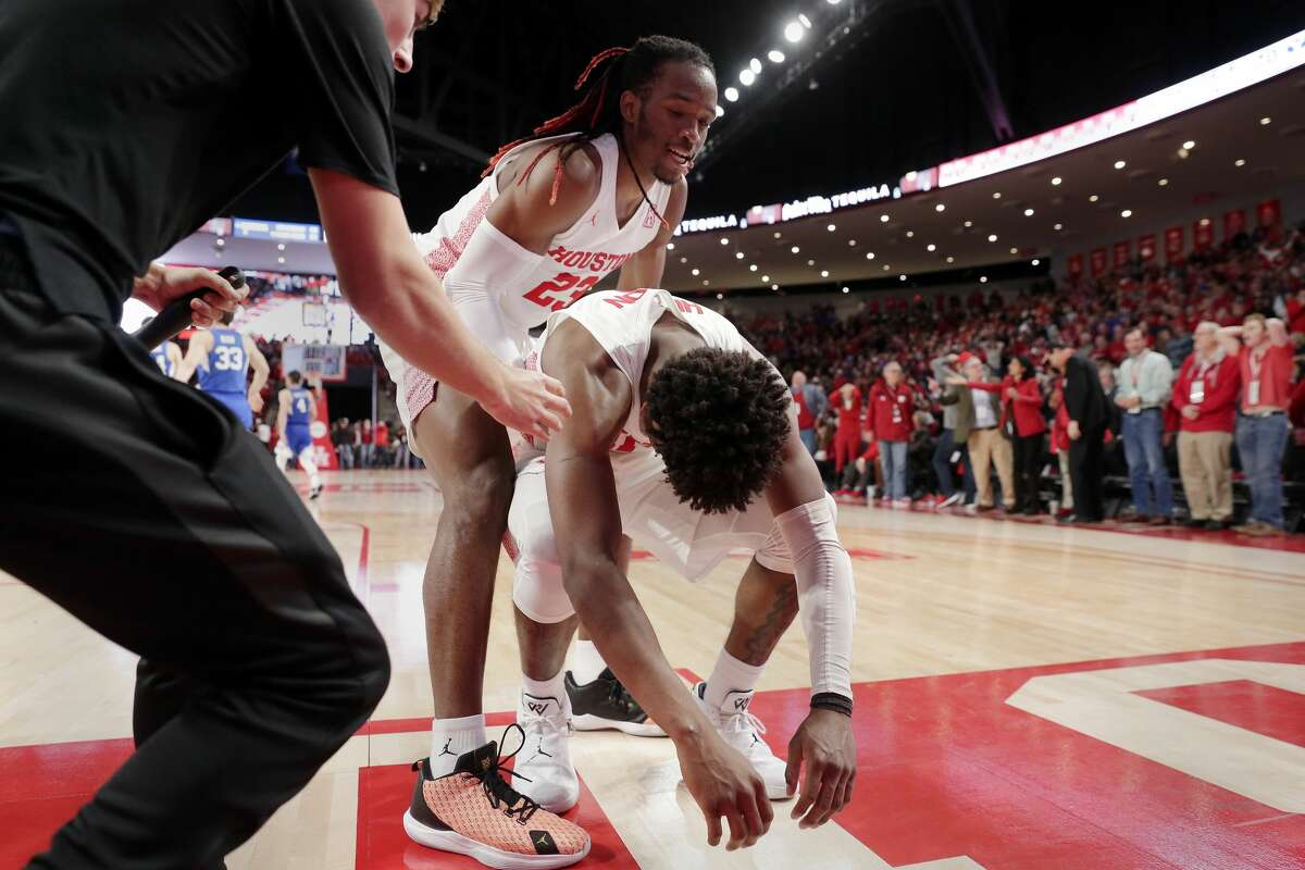 Houston guard Nate Hinton (11) is consoled by forward Cedrick Alley Jr. (23) after Hinton was called for a foul as he drove for a basket in the final seconds during the second half of their NCAA basketball game against Brigham Young Friday, Nov. 15, 2019 in Houston, TX.