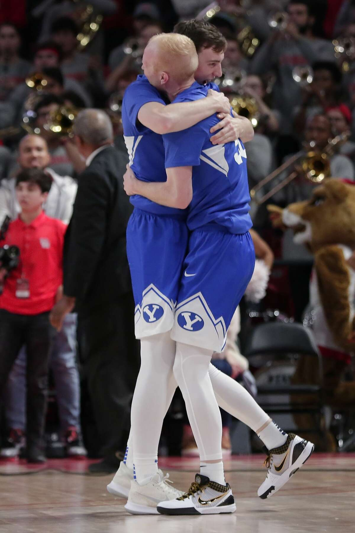 Brigham Young guard Evan Troy, left, hugs Brigham Young guard TJ Haws, right, after Haws' last second basket to win by one point after their NCAA basketball game against Houston Friday, Nov. 15, 2019 in Houston, TX.