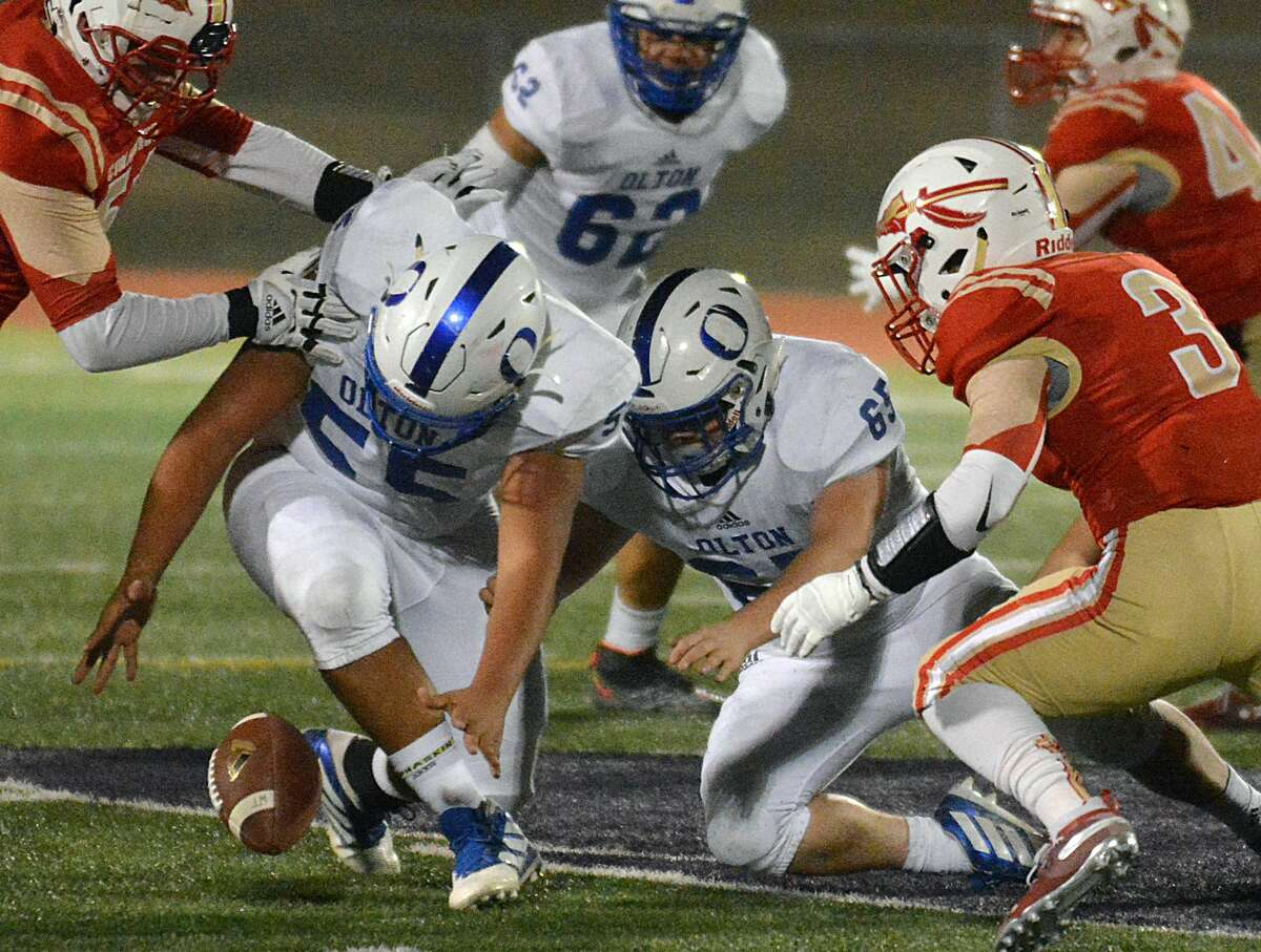 Olton defenders Dean Rios and Andru Garcia (65) come up with the fumble recovery.