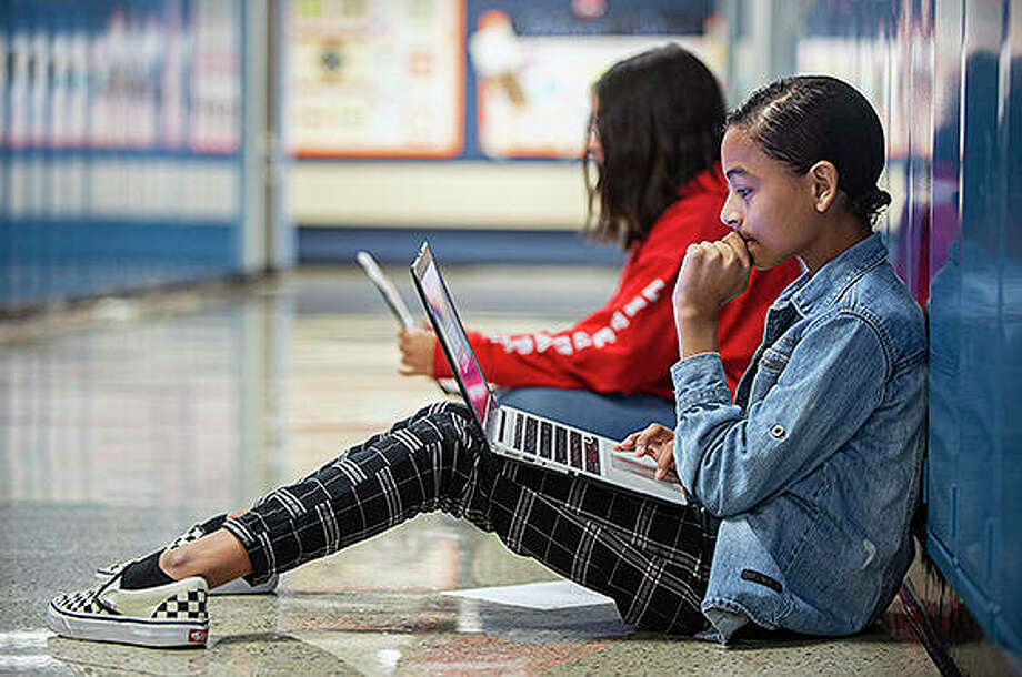 Fawlco Ramos, 13, a seventh grade student, takes a seat in the hallway and uses a laptop to do classwork. While some school districts within the same community have the newest tech, other districts are not so fortunate. Photo: Rick Kintzel | The Morning Call (AP)