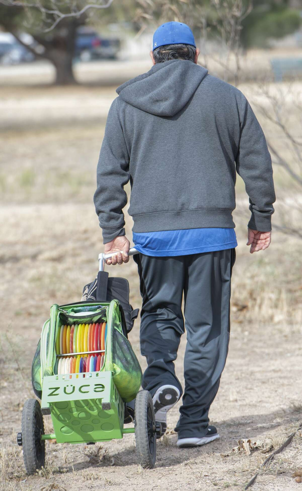 Angel Acosta, like many others, carries his varying discs in a pull behind so he has just the right one available for each shot 11/16/19 at the 8th annual Oilfield Blowout Low Putt Disc Golf Tournament at Windlands Park. Tim Fischer/Reporter-Telegram