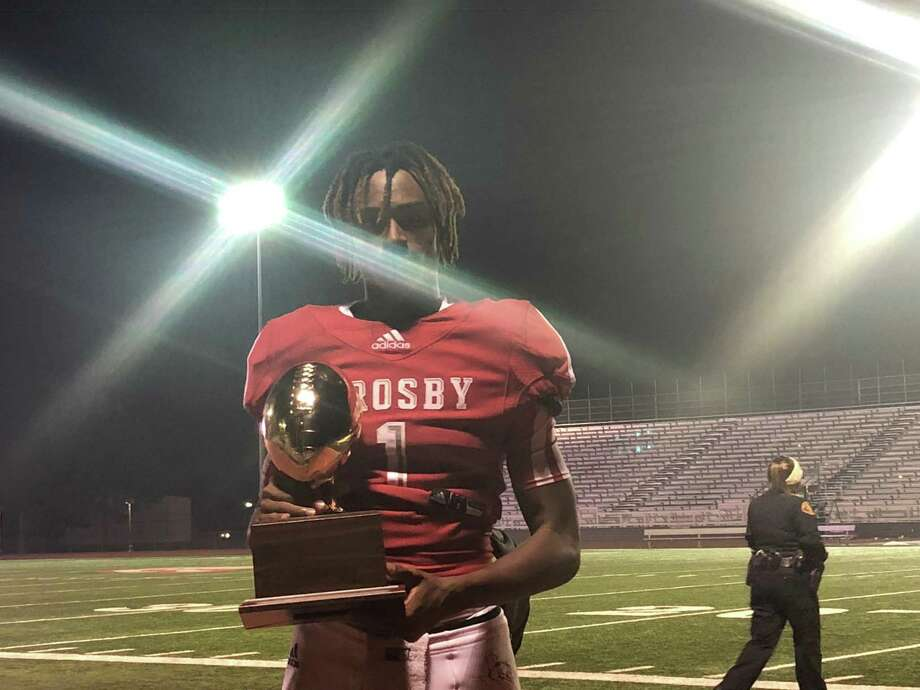 Crosby's Reggie Branch holds the Bi-District trophy after the Cougars beat the Fort Bend Willowbridge Eagles 70-42 at Cougar Stadium in Crosby on Nov. 15 Photo: Elliott Lapin / Staff Photo