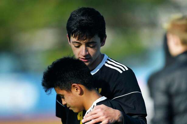 Voorheesville's Dylan Ensslin, bottom, is consoled by Conrad Becker after their loss in a NYSPHSAA Boys Soccer Championships Class C semifinal in Middletown, N.Y., Saturday, Nov. 16, 2019. Voorheesville's season ended with a 1-0 loss to Rhinebeck-IX. (Adrian Kraus / Special to the Times Union)