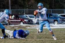 Meridian's Cameron Metzger looks for a teammate to pass to during the Mustangs' 48-14 regionals loss to Montague Saturday, Nov. 16, 2019 at Montague High School. (Daytona Niles/for the Daily News)