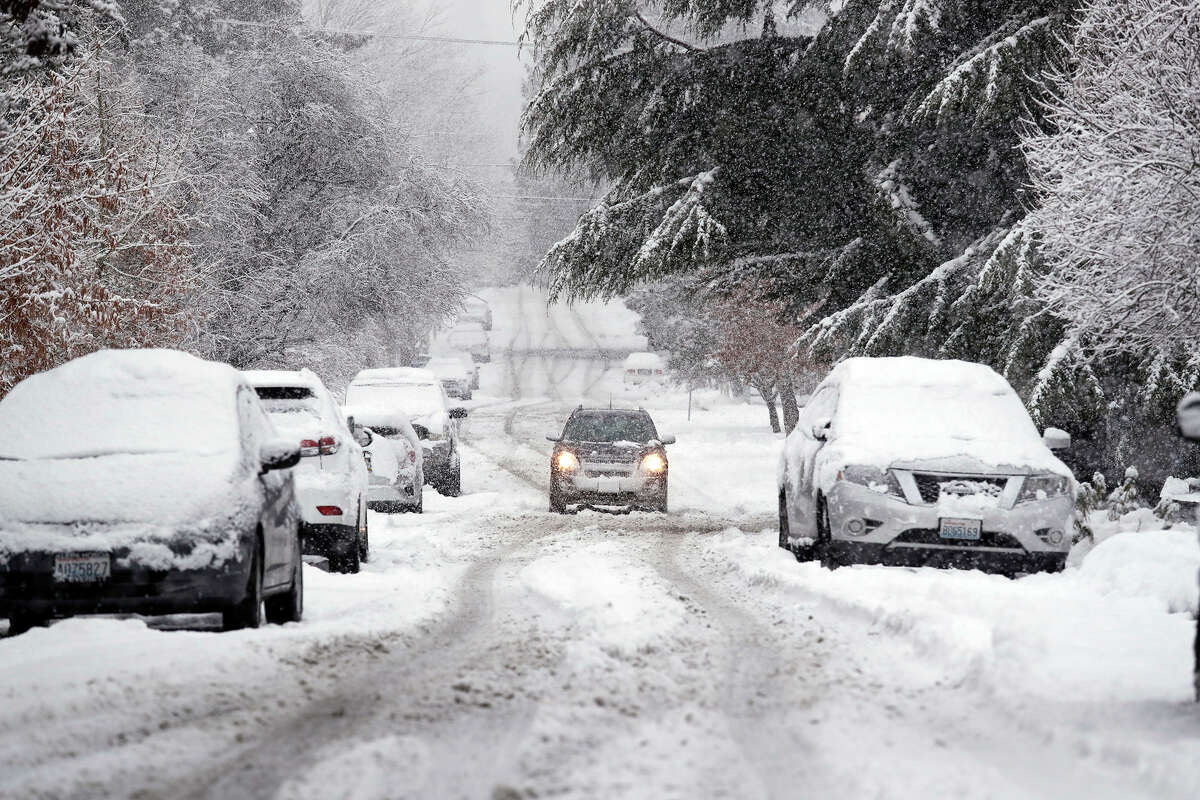 FILE - In this Feb. 11, 2019, file snow piles up on a street as a car maneuvers down the street in Seattle. With the eastern two-thirds of the U.S. shivering through an early blast of arctic air, ita€™s time to start thinking about whether your cara€™s tires will get you safely through the winter. (AP Photo/Elaine Thompson, File)