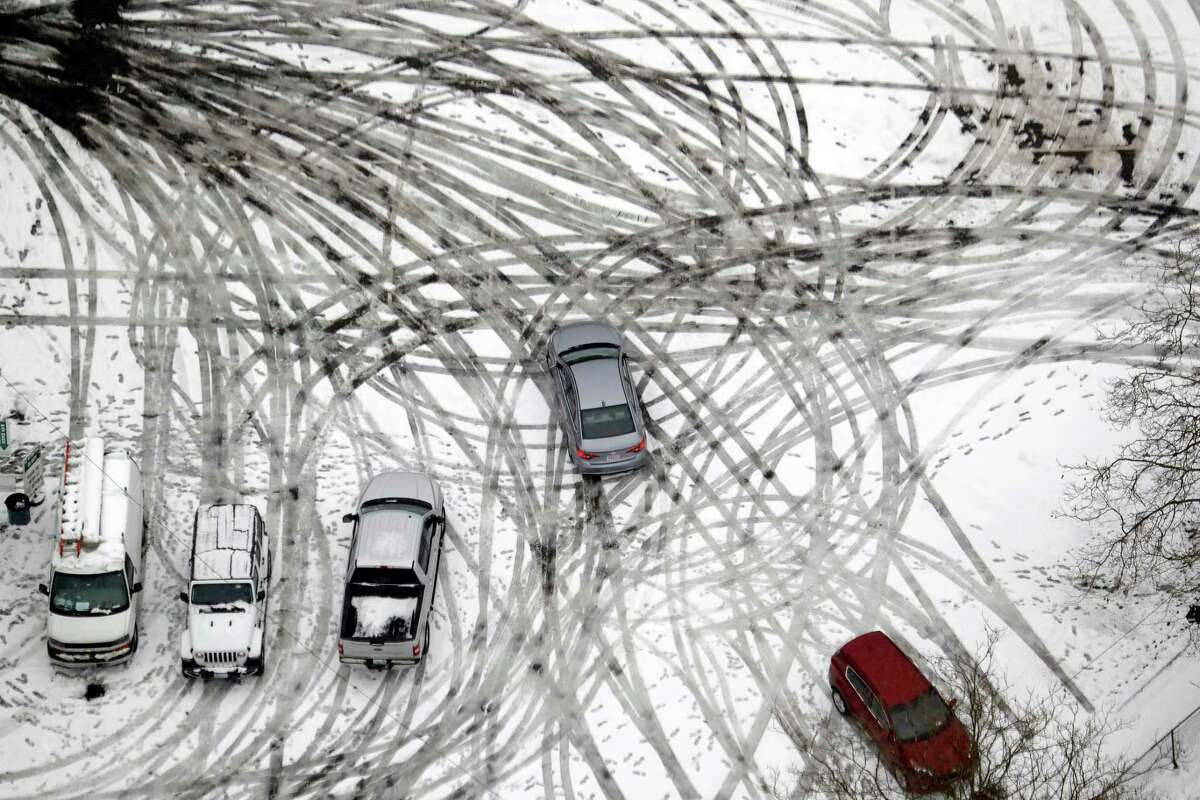 FILE - In this Feb. 11, 2019, file photo a car maneuvers through a still snow-covered parking lot in Seattle. With the eastern two-thirds of the U.S. shivering through an early blast of arctic air, ita€™s time to start thinking about whether your cara€™s tires will get you safely through the winter. (AP Photo/Elaine Thompson, File)