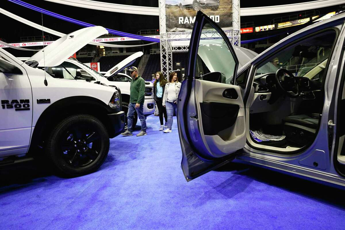 Adults and children look over the various cars on display at the Albany Auto Show at the Times Union Center on Sunday, Nov. 3, 2019, in Albany, N.Y. Thirty manufacturers were on display at the three-day show. (Paul Buckowski/Times Union)