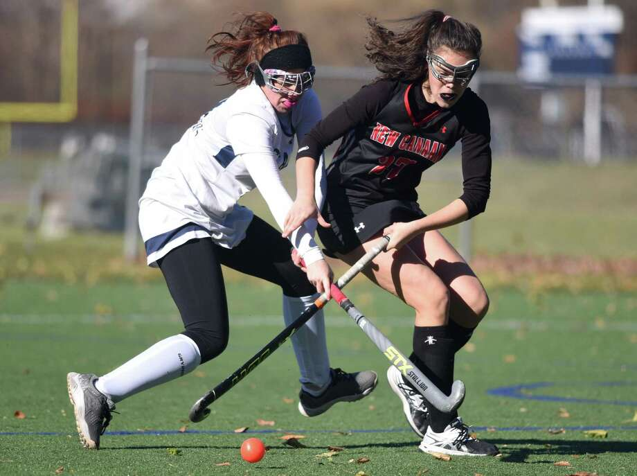 Staples' Ella Bloomingdale (9) and New Canaan's Caroline Brooks (27) battle for the ball during a Class L field hockey quarterfinal game in Westport on Saturday. Photo: Dave Stewart / Hearst Connecticut Media / Hearst Connecticut Media