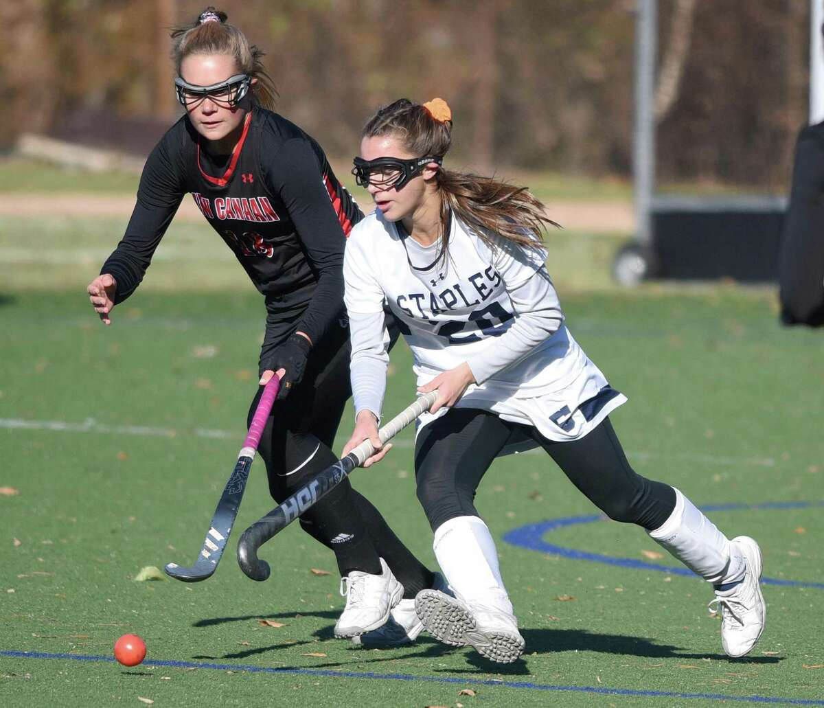 Staples' Jessica Leon (20) takes the ball through the midfield while New Canaan's Anna Lindeis (18) pursues during a Class L field hockey quarterfinal game in Westport on Saturday.