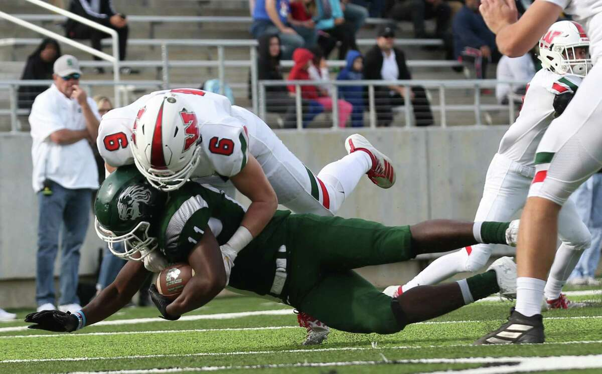 Spring Lions wide receiver Travis Sims Jr. (11) is tackled by The Woodlands Highlanders defensive back Dylan Binney (11) in the first half at Planet Ford Stadium on November 16, 2019 at in Spring, TX.