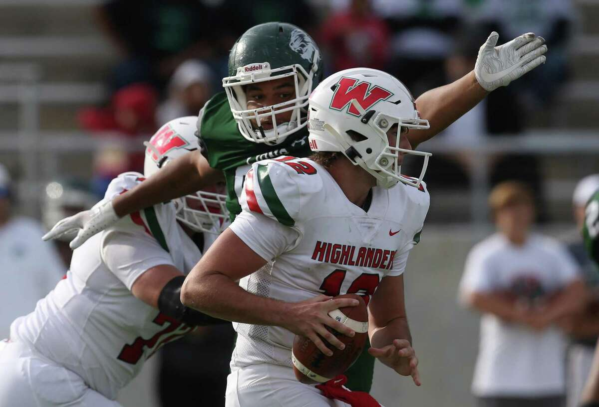 The Woodlands Highlanders quarterback Ben Mills (12) is sacked by Spring Lions defensive lineman Calvin Broussard II (94) in the first half at Planet Ford Stadium on November 16, 2019 at in Spring, TX.
