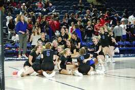 Friendswood players and coaches celebrates a four-set victory over Manvel Saturday in the Region III-5A volleyball championship match at Delmar Fieldhouse.