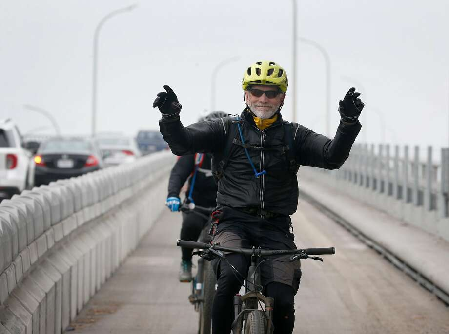 A cyclist displays his pleasure as he completes his first ride across the Richmond-San Rafael Bridge on the new bike path. Photo: Paul Chinn / The Chronicle
