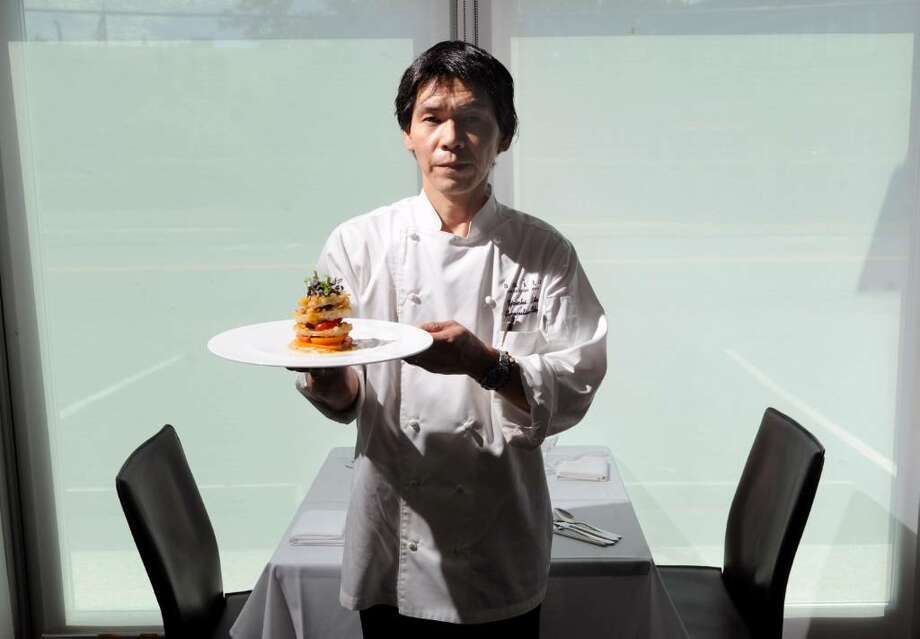 Chef Yoichi Saito poses inside his French Asian fusion restaurant, Saito, at 249 Railroad Avenue, Greenwich, Conn., with a heirloom tomato salad, Thursday, July 22, 2010. Photo: Bob Luckey / Greenwich Time