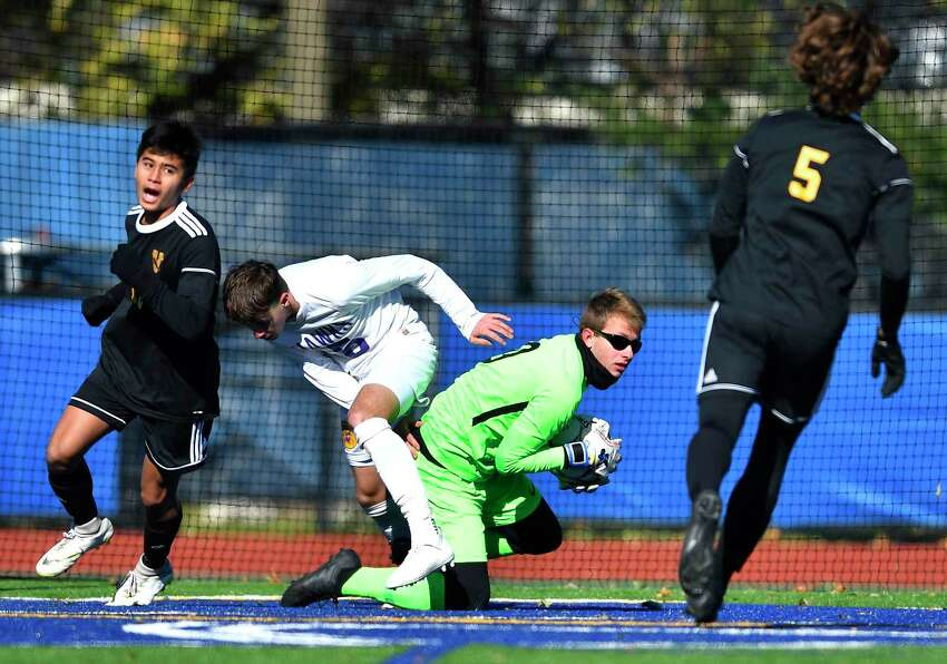 Voorheesville goalie Trevor Guilmette, makes a save while pressured by Rhinebeck's Jonathan Lange during a NYSPHSAA Boys Soccer Championships Class C semifinal in Middletown, N.Y., Saturday, Nov. 16, 2019. Voorheesville's season ended with a 1-0 loss to Rhinebeck-IX. (Adrian Kraus / Special to the Times Union)