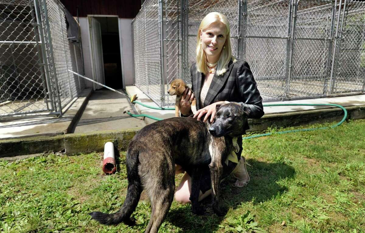 Tails of Courage, a dog rescue and adoption program started by local immigration attorney Kristan Exner, has a new home on Pembroke Road in Danbury, Conn. Exner is photographed with two of her own dogs at the kennel Monday, July 29, 2013.