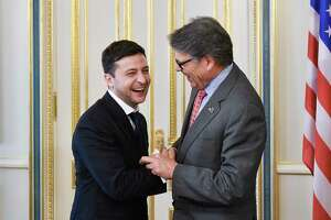 FILE - In this May 20, 2019, file photo, Ukrainian President Volodymyr Zelenskiy, left, and Energy Secretary Rick Perry share a joke during their meeting in Kiev, Ukraine. Michael Bleyzer and Alex Cranberg, two political supporters of Perry secured a potentially lucrative oil-and-gas exploration deal from the Ukrainian government soon after Perry proposed one of the men as an adviser to the country's new president. (Mykola Lazarenko/Presidential Press Service Pool Photo via AP)