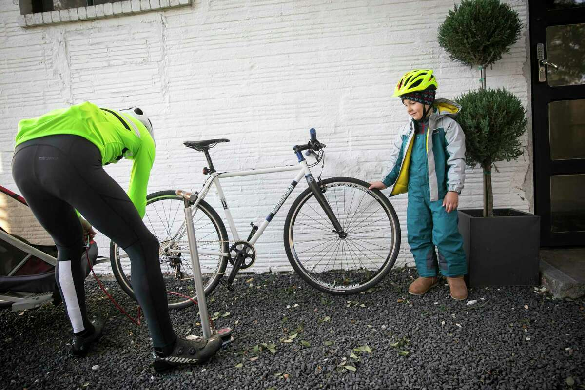 Samih Elchahal and his son, Dean, 5, prepare for a morning group bike ride on Nov. 16, 2019, outside the Bicycle Speed Shop in the Heights. The family ride was organized to raise awareness for No Kid Hungry by former pro cyclist Phil Gaimon, starting from the shop.