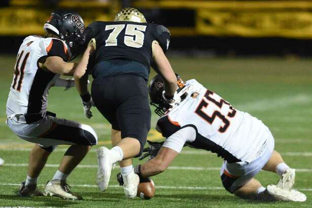 Philip Sissick (right) of Shelton recovers a fumble in the second half against Daniel Hand in Madison.