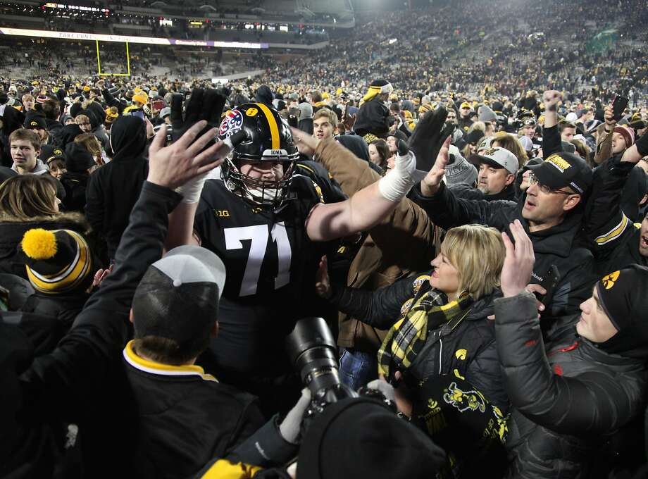 Iowa offensive lineman Mark Kallenberger greets fans in Iowa City who stormed the field after the 23-19 win over previously unbeaten Minnesota on Saturday. Photo: Matthew Holst / Getty Images