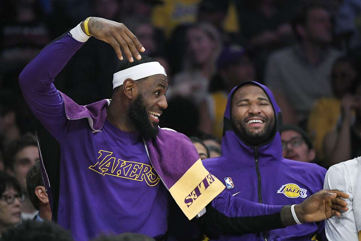 Los Angeles Lakers forward LeBron James, left, jokes around with center DeMarcus Cousins on the bench during the second half of the team's preseason NBA basketball game against the Golden State Warriors on Wednesday, Oct. 16, 2019, in Los Angeles. The Lakers won 126-93. (AP Photo/Mark J. Terrill)